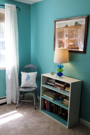 photo of chair, bookshelves with lamp and artwork