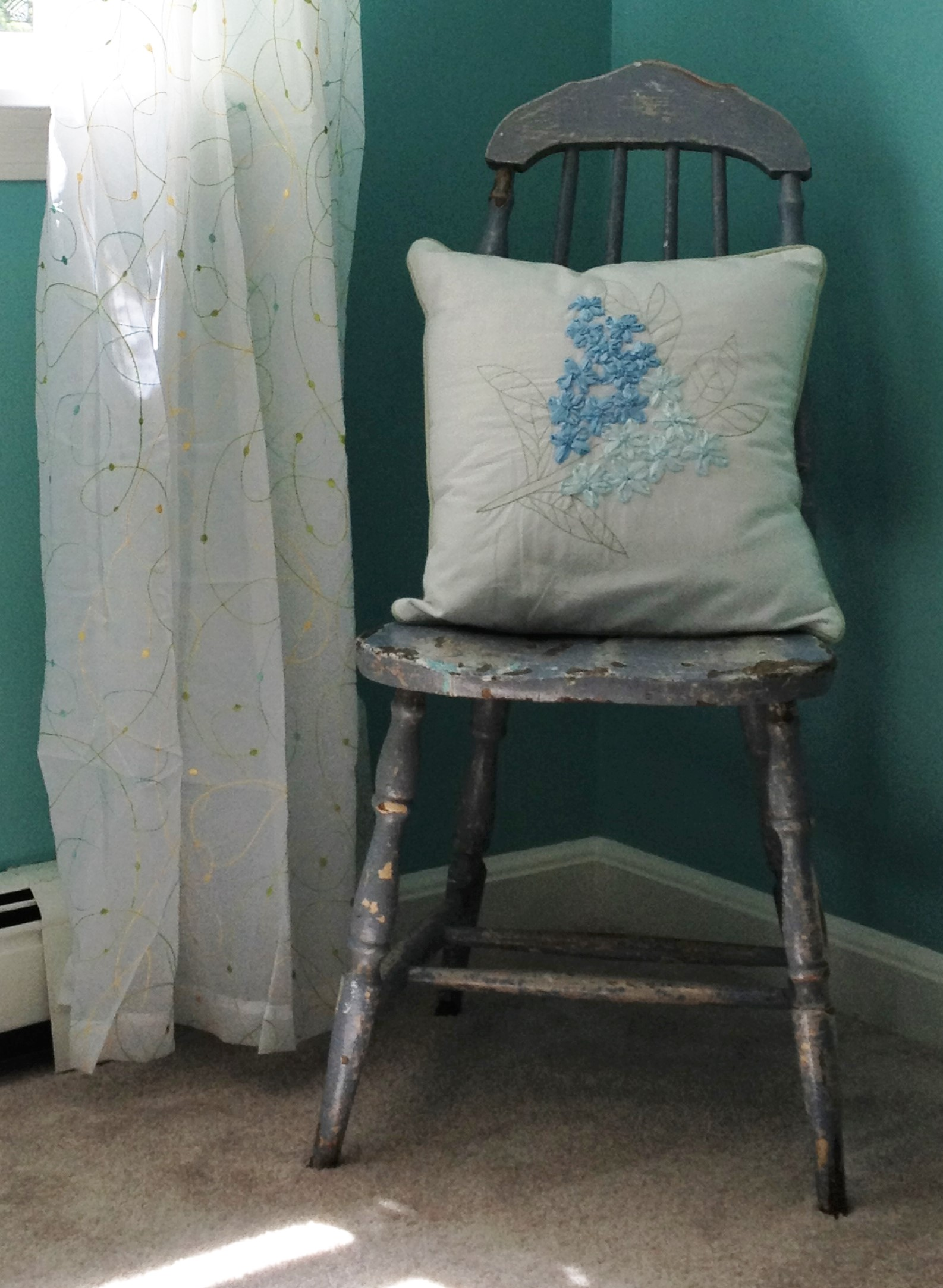 photo of vintage paint chipped chair with pillow